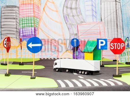 Picture of a white lorry turning on road crossing in the toy city model