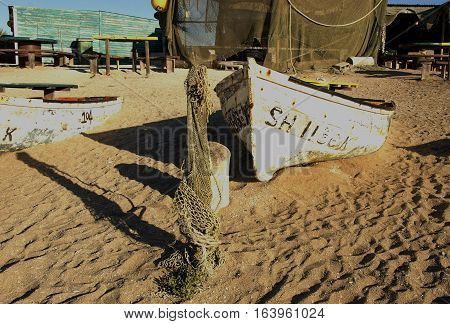 old wooden boat lying on the shore in the bushes of flowers and sand, selective focus