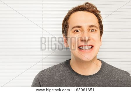 Portrait of smiling young man with metal and ceramic dental braces