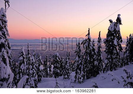 City view at sunset in winter. Grouse Mountain. North Vancouver. British Columbia. Canada.