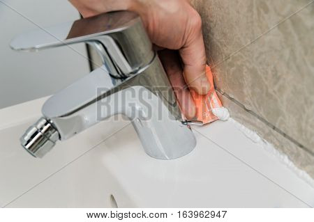 Worker smoothing silicone sealant between the bidet and the wall using a spatula.