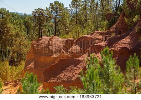 Oragne ochre picturesque hills. Village Roussillon Provence France, Luberon park. Preserve natural dye production - ocher.