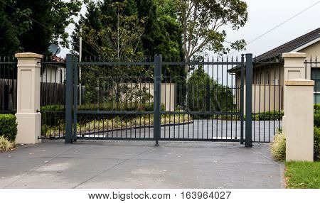 Black wrought iron driveway entrance gates set in fence