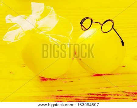 on light wood chopping board are a pair of lovers kissing and yellow lemons boy in dark glasses and a girl with a white bow on a horizontal surface with top view and front