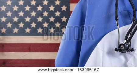Closeup of medical doctor scrubs with stethoscope against faded boards painted in USA flag background. Healthcare concept for America.