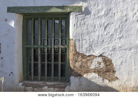 Window on a old adobe building showing signs of wear and peeling plaster