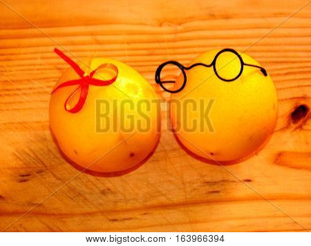 on light wood chopping board are a pair of lovers of yellow lemons boy in dark glasses and a girl with a bow in red and yellow on a horizontal surface with top view and front