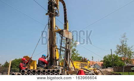 Workers on Drilling Rig. A worker prepares to join two pieces of drill pipe on a drilling rig.