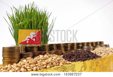 Bhutan Flag Waving With Stack Of Money Coins And Piles Of Wheat And Rice Seeds