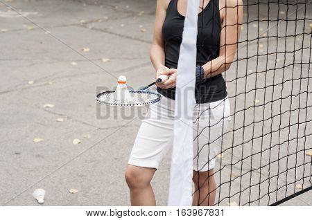 Girl holding a racket with a badminton shuttlecock