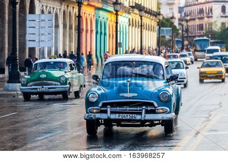 Havana, Cuba 2016.01.22 Retro classic American cars drive on the rainy roads round Parc Centrale in Havana, Cuba.