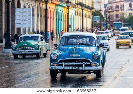 Havana, Cuba 2016.01.22 Retro classic American cars drive on the rainy roads round Parc Centrale in Havana, Cuba.