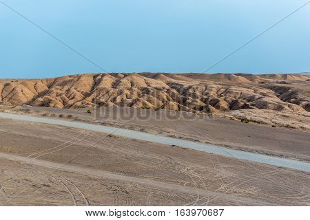 Crusted sand dunes and a road on Maranjab Desert in Iran