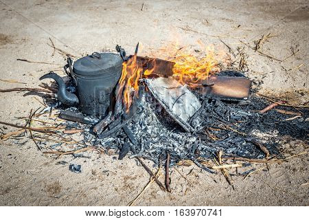 kettle of water for tea boiling on fire on Maranjab Desert in Iran