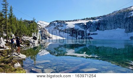 Friends taking pictures at alpine lake.  Inspiration lake. Enchantment Lakes. Cascade Mountains. Leavenworth. Washington. United States.