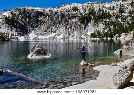 Woman meditating by alpine lake. Vivian Lake. The Enchantments. Leavenworth. Seattle. Washington. United States.