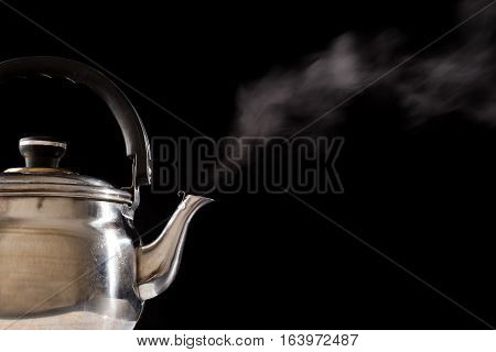 Steam from boiling water in teapot isolated on black background, empty space for text