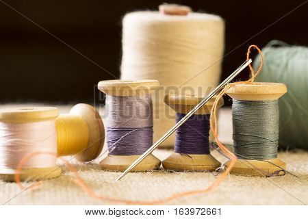 Collection of color thread spools with needle on canvas background.
