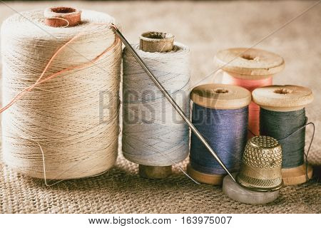 Collection of color thread spools with needle and thimble on canvas background. Vintage toned photo.