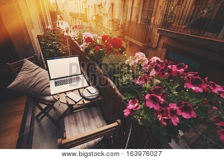 Small cozy beautiful workspace on balcony with laptop smartphone and two chairs and a lot of flowers around on sunny summer day with narrow street behind in historical district of Barcelona - El Born
