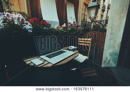 Small cozy beautiful workspace on balcony with laptop mouse smartphone chair lantern wooden fence and flowers around on summer day facade of house behind Barcelona El Born district Spain