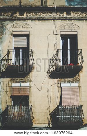 Close-up view of facade with balconies and four windows with closed and opened jalousie old house in touristic and historical district of Barcelona -El Born sunny summer day Spain