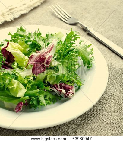 Green salad with spinach, frisee, arugula, radicchio, feta cheese and black sesame seed on blue wooden background, square, toned