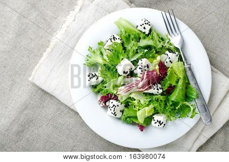 Green salad with spinach, frisee, arugula, radicchio, feta cheese and black sesame seed on blue wooden background, top view