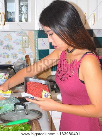 Asian female beauty cooking ground beef in her kitchen at home.