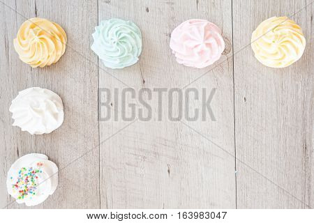 Top view background with meringues in pastel colors.