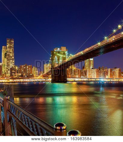 Brooklyn Bridge and Manhattan Skyline At Night, New York City Hudson River with skyline after sunset night view illuminated with lights viewed from Brooklyn.