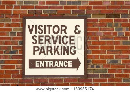 Business sign directing visitors and service representatives to parking area and entrance