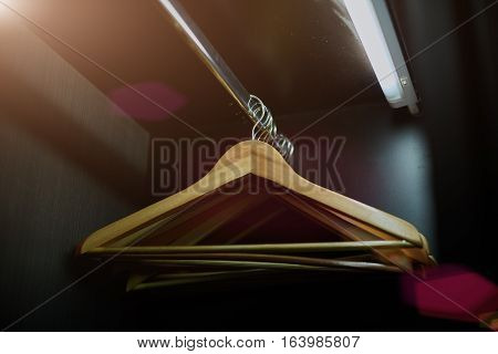 Wooden hanger hanging in an empty closet on the upper