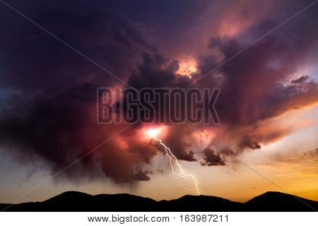 Lighting bolt striking from colorful clouds at sunset in the Nevada desert