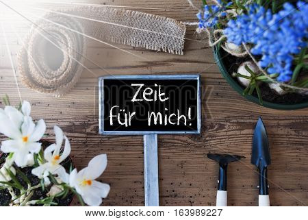 Sign With German Text Zeit Fuer Mich Means Time For Me. Sunny Spring Flowers Like Grape Hyacinth And Crocus. Gardening Tools Like Rake And Shovel. Hemp Fabric Ribbon. Aged Wooden Background