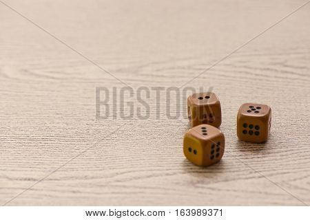 Brown dices on wooden background. Concept of luck, chance and leisure fun.