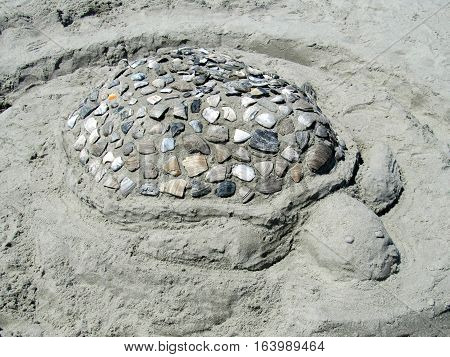 Sandcastle of a sea turtle made of sand and seashells
