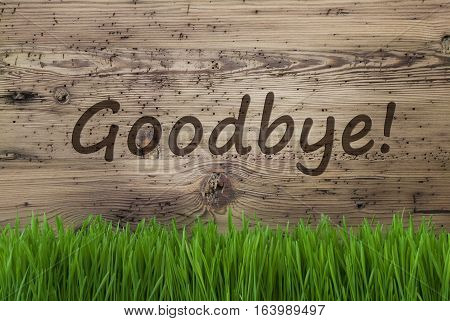 English Text Goodbye. Spring Season Greeting Card. Aged Wooden Background With Gras.