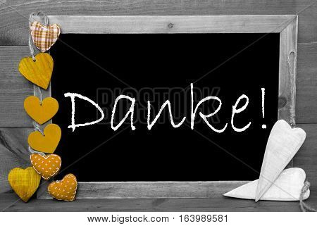 Chalkboard With German Text Danke Means Thank You. Yellow Hearts. Wooden Background With Vintage, Rustic Or Retro Style. Black And White Image With Colored Hot Spots.