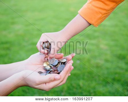 abstract money saving for family. kid hand is holding coins to put on or give to mother hands that holding another coins with green grass background