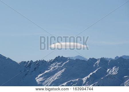 A lenticular cloud above alpine mountain peaks