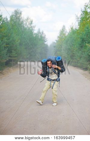 Young happy man in hoodie with heavy backpack and two travel rugs is on road through forest waving his hands and laughing merrily. Hiking in the woods. Sport and concept of a healthy lifestyle.