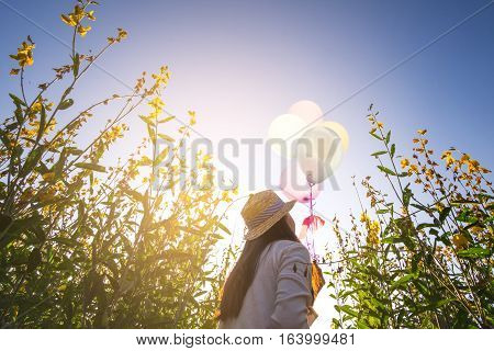 Girl Running On The Field Of Yellow Flowerwith Balloons At Sunset. Happy Woman On Nature, Concept Ab