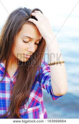 Portrait of pensive beautiful woman in a plaid shirt with drooping eyes by the sea.