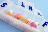 A pillbox with mutli colored pills and vitamins against a blue background poster