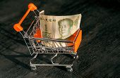 Shopping cart with a paper banknote of One Chinese Yuan and face of leader Mao, as a symbol of the modern international economy poster