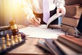 Young lawyer business man working with paperwork on his desk in office workplace for consultant lawyer concept of photography vintage tone with sunlight effect. poster