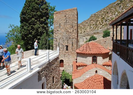TILOS, GREECE - JUNE 17, 2018: Tourists walk round the Byzantine period monastery of Agios Panteleimon on the Greek island of Tilos. The monastery dates from circa 1470.