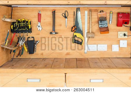 Wooden workbench at workshop. Lot of different tools for diy and repair works. Wood desk for product display. Copyspace. Labour day poster