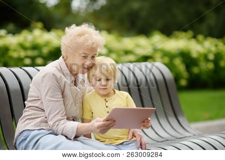 Beautiful Granny And Her Little Grandchild Together In Park. Grandma And Grandson Seating On The Ben